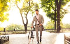 42718036 - confident young businessman walking with bicycle on the street in town