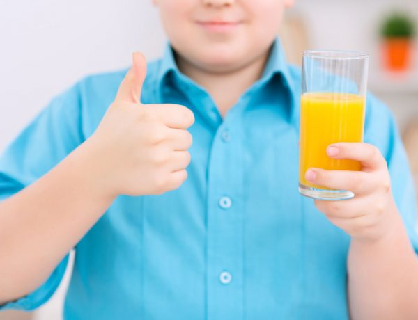 50835216 - healthy drink. chubby boy is holding a glass of orange juice and showing thumbs up.
