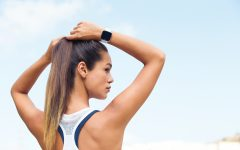 Lifestyle photo of young female on outdoor run adjusting hair showing product on arm