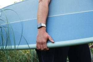 Lifestyle photo of young male holding surfboard, close up of arm wearing product